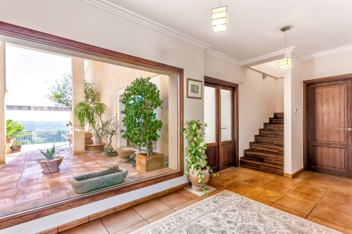Entrance hall with panorama window and views to the mediterranean patio
