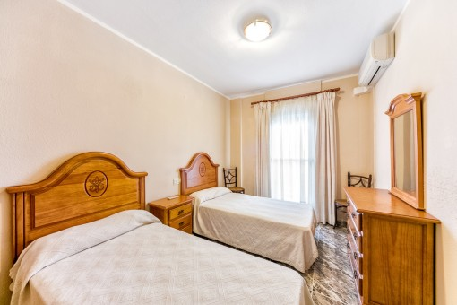 Bedroom with two single beds and air conditioning