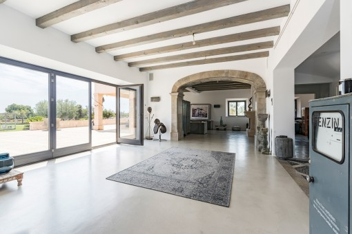Large living area with stone arches and wooden ceiling beams