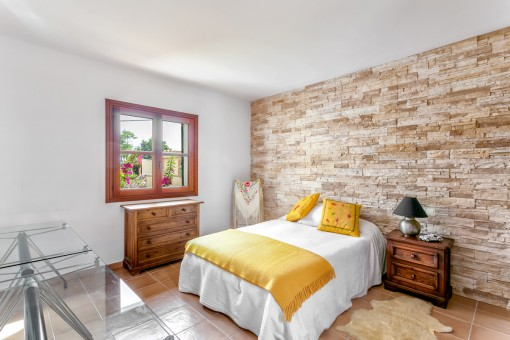 Double-bedroom with stone wall